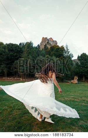 Gorgeous Bride Dancing In Sunlight In Mountains. Happy Stylish Wedding Bride In Gown And Sneakers In