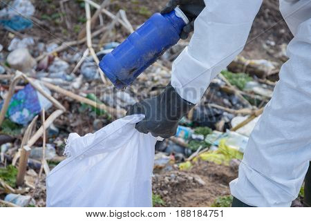A volunteer man in white protective clothing collects garbage. Hand close up