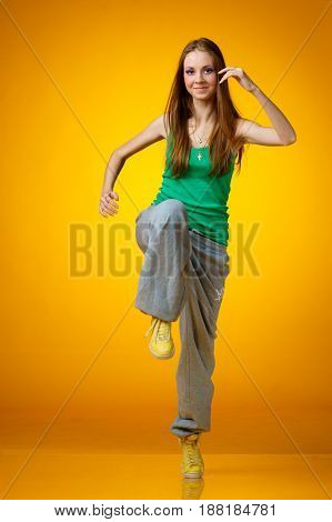 young teenager female dancing on yellow background