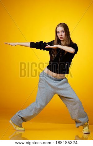 teenager girl dancing hip-hop and looking in camera