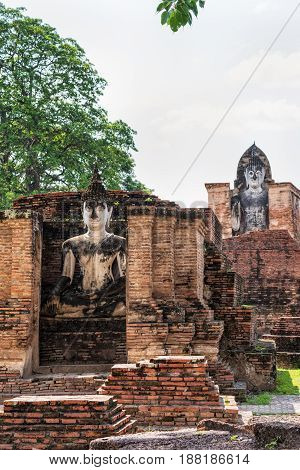 Ancient Buddha statue among the ruins under the bright sun of Wat Maha That temple in Sukhothai Historical Park is an old city and famous tourist attraction of Sukhothai Province Thailand