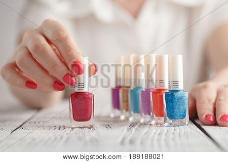 Palette of colorful nail polishes on white