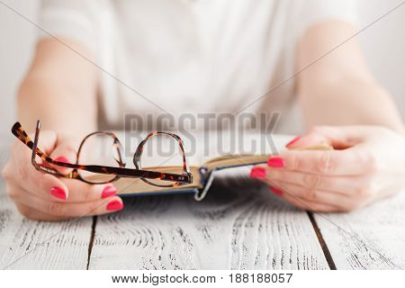 Woman Reading A Book And In Her Hand She Holds A Pair Of Eyeglasses