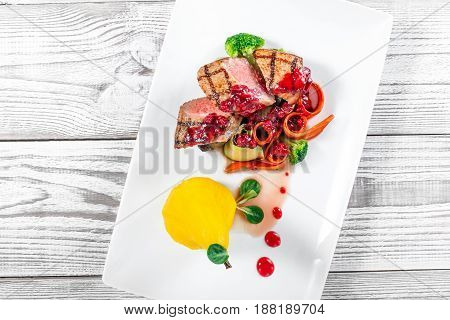 Grilled medium rare beef with pear grilled vegetables broccoli berries sauce on plate on wooden background close up. Hot Meat Dishes. Top view