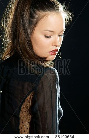 studio portrait from the back of young beautiful and sexy woman in black tranparent blouse with closed eyes on black background and in back light
