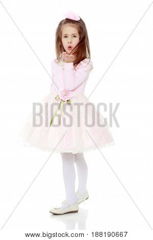 Dressy little girl long blonde hair, beautiful pink dress and a rose in her hair.She sends a kiss.Isolated on white background.