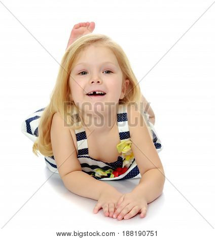 Pretty little blonde girl summer striped dress lying on the floor and smiling at camera.Isolated on white background.