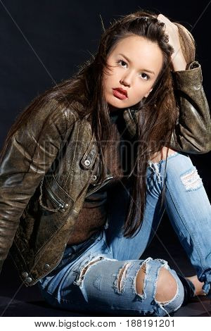 fashion style photo of young attractive woman sitting and looking at you