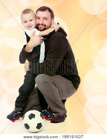 little boy who loves to play football embraces his beloved father.Brown festive, Christmas background with white snowflakes, circles.