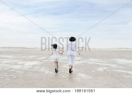 Happy Asian family during summer vacation. Asian Mother and child daughter run laugh and play at tropical beach.