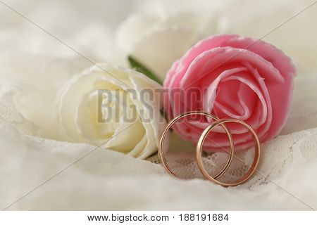 Wedding rings with rose on white lace