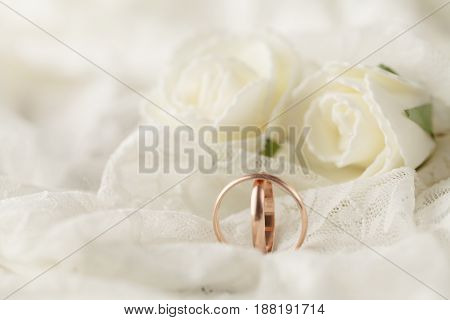 Pair Of Golden Wedding Rings Over Invitation Card Decorated With Lace