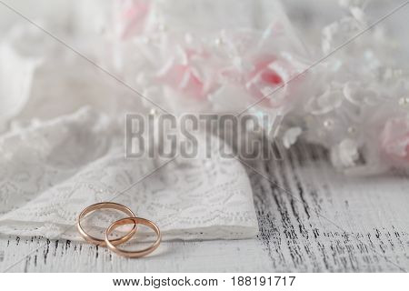 Wedding rings on white lace background with flowers