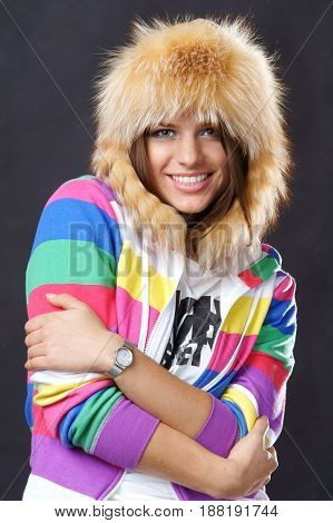 smiling woman in colourful jacket and fur hat looking at you