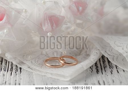 Wedding rings on white satin ;ace background