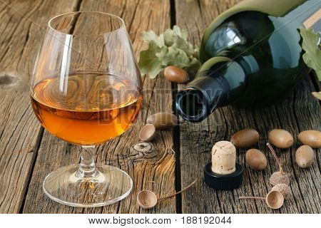Glass Of Brandy Or Cognac On Old Oak Wooden Table