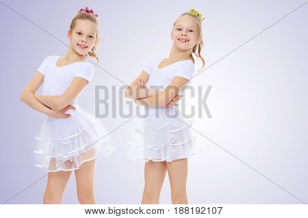 2 cheerful girls twins in white gymnastic costumes posing for the camera.On a light purple gradient background.