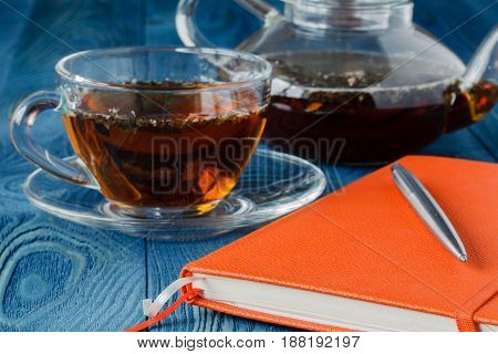 cup of tea on wooden table with notebook