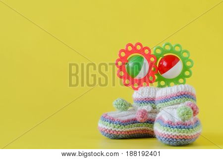 Newborn Announcement. Knitted Baby Booties On Plain Yellow Background