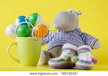 Hippopotamus toy and green cup of rattles