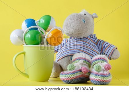 Hippopotamus toy and green cup with rattles