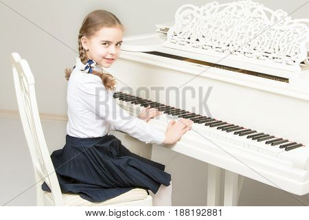Charming little blonde with long wattled hair in plaits, playing on a white grand piano. In musical school.