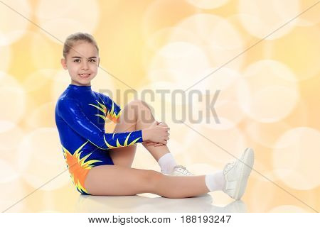 A charming gymnast girl, a younger school age, in a beautiful blue swimsuit, performs an exercise on the floor.Hand clasp by the knee.Brown festive, Christmas background with white snowflakes, circles.