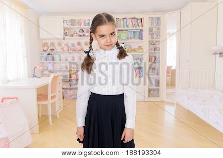 A beautiful little schoolgirl girl in a white blouse and black long skirt, with neatly braided pigtails on her head.She is standing right in front of the camera.Close-up.In the children's room.