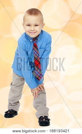 Cute little blonde boy in a Blue shirt and tie.Brown festive, Christmas background with white snowflakes, circles.