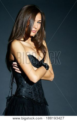 beautiful stylish woman with perfect breast in black corset looking in camera