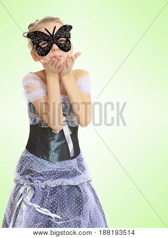 Slender little girl , with beautiful hair on his head, elegant long Princess dress.Posing in carnival mask.She sends a kiss.