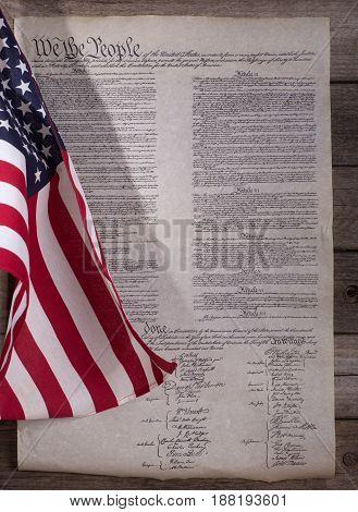 American flag and United States constitution on a wood background