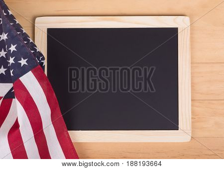 American flag next to a chalk board on a wood background