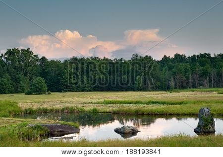 Tranquil Pond with Sculptural Rocks and Golden Meadow at Sundown in the Catskills of the Hudson Valley in Upstate NY.