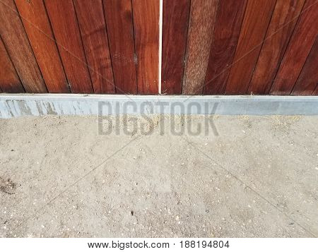 light brown dirt and dark brown wood wall