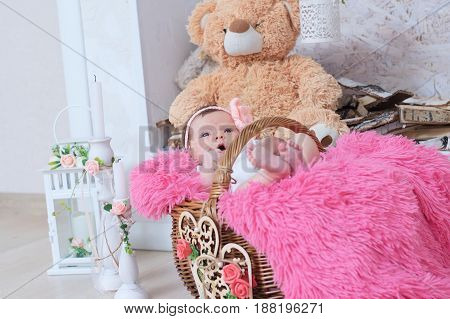 newborn in basket baby girl daughter. Cute decoration with pink blanket candles toy bear and hearts. New child announcement