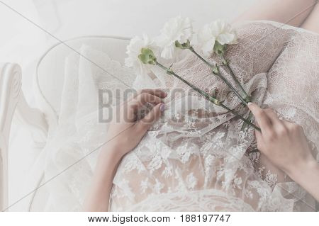 Flowers lie on the lap of a sweet girl. She is wearing a white dress. Bride in anticipation of the ceremony. Man is unrecognizable.