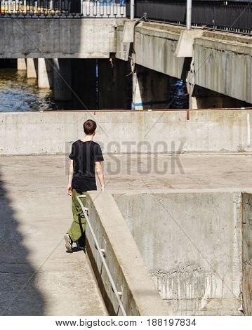 Young man walking on the pier. Parkour in the urban space. Sports in the city. Sport activity.