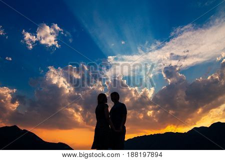 Silhouette of a newly-married couple on the background of the setting sun in Perast in Montenegro.