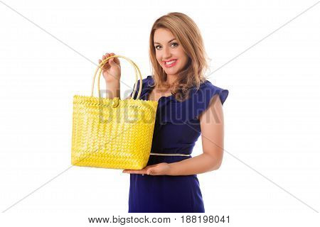 Pretty woman in blue dress with bright wicker yelow tote bag.Isolated on the white studio background