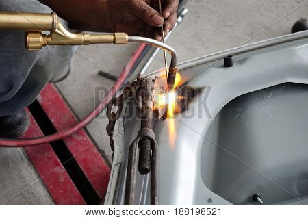 Welding auto body with gas torch - Auto repair shop