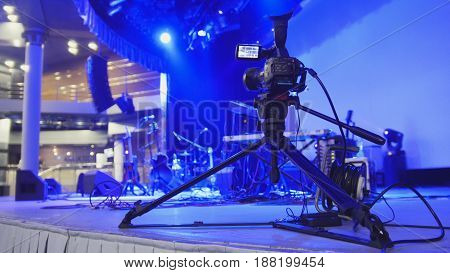 Abstract blurred - video camera stands on the stage in the concert hall before the concert