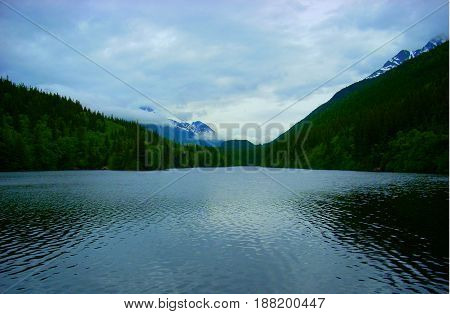 Lake surrounded by mountains on a cloudy day