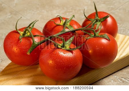 Bunch Of Red Ripe Tomatoes On A Cutting Board