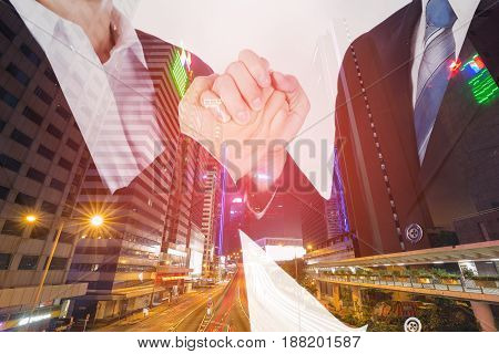 double exposure of arm wrestling between businessman and businesswoman with a city background