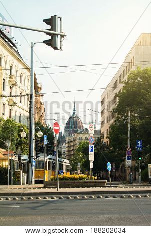 BUDAPEST HUNGARY - JULY 24 2016: A crossroad of Budapest with plenty of signs a street light a tram and a view to Parliament building.
