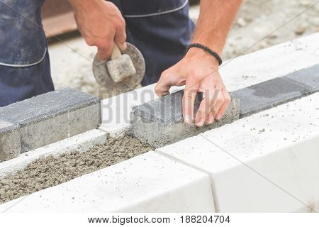 Construction worker working hard leveling concrete pavement outdoors.