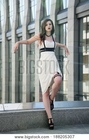 Young beautiful sexy woman wearing trendy outfit, white dress and leather swordbelt. Longhaired brunette posing in the city street. Outdoor fashion photography.