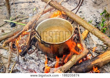 Cooking outdoors in the open air boils broth in a metal bowler bubbles appeared
