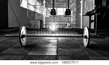 Barbell on floor in gym. Black and white photo